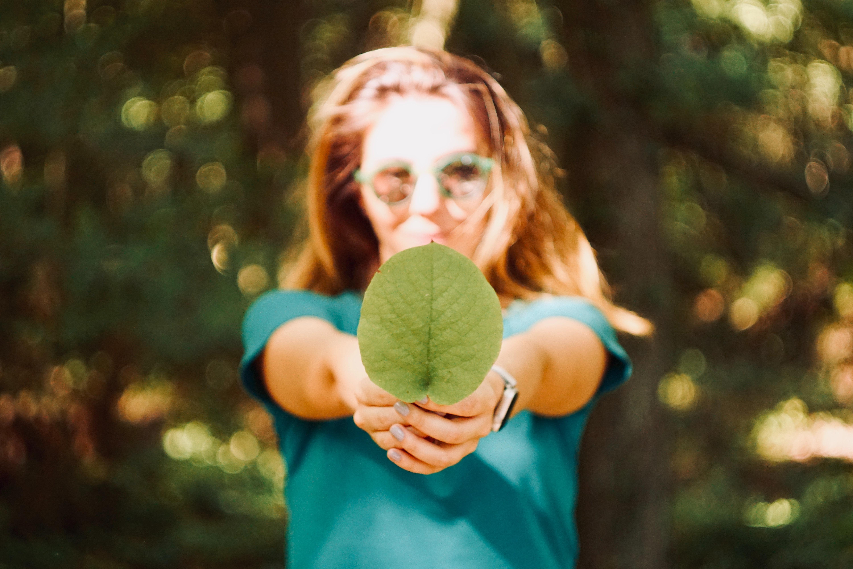 fille tenant une feuille d'arbre